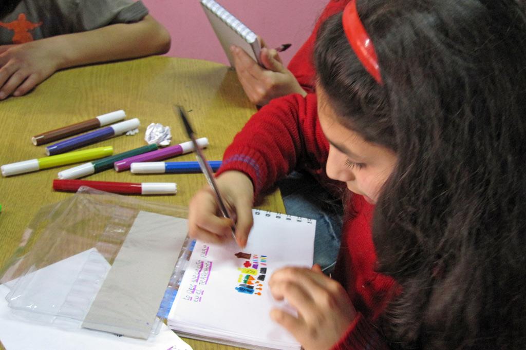 Mädchen malt mit bunten Stiften