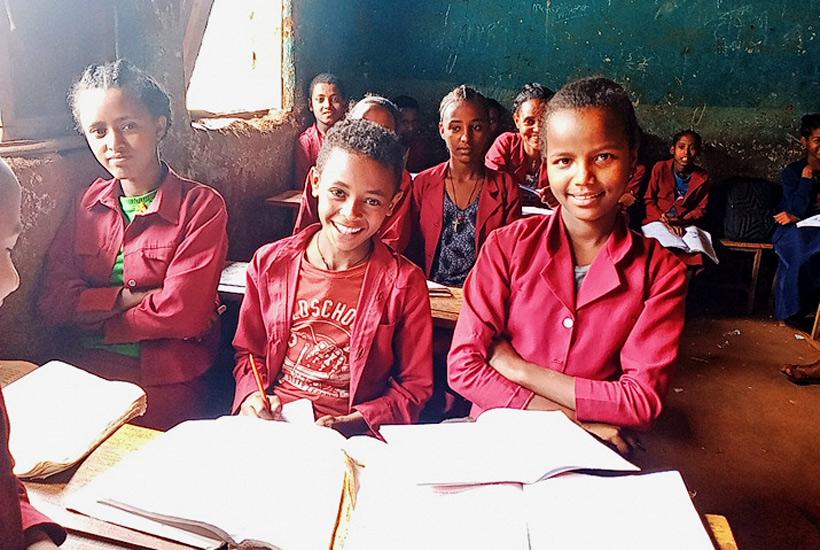 Ayana mit Schulfreundinnen im Klassenzimmer - sie hat die Kinderarbeit hinter sich gelassen