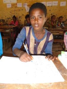Adamluk schreibt etwas an seinem Tisch in der Schule, die er besuchen kann, obwohl er Opfer von Kinderhandel ist.