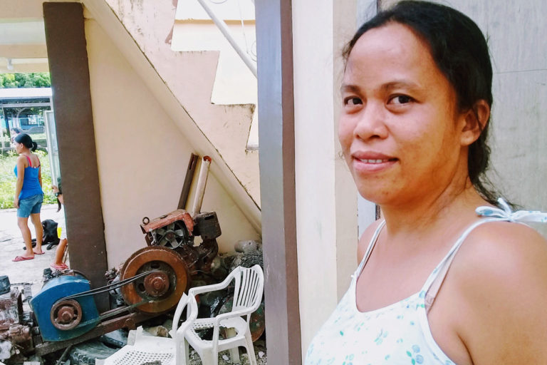 Im Vordergrund eine Filipina, im Hintergrund eine Maschine