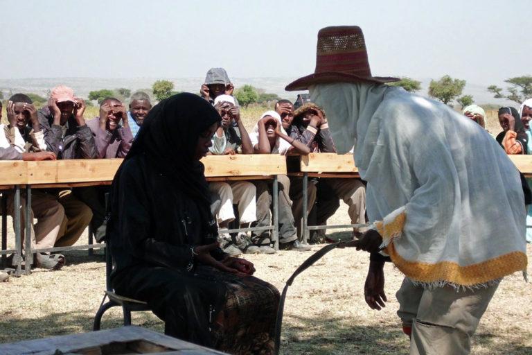 Ein Mann steht vor einer verhüllten Frau. (Quelle: NAFIS)