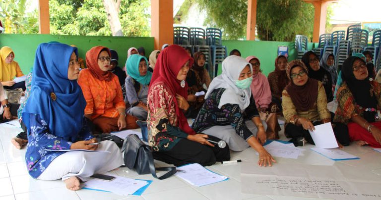Frauen sitzen auf dem Boden und blättern in ihren Unterlagen (Quelle: AMURT)