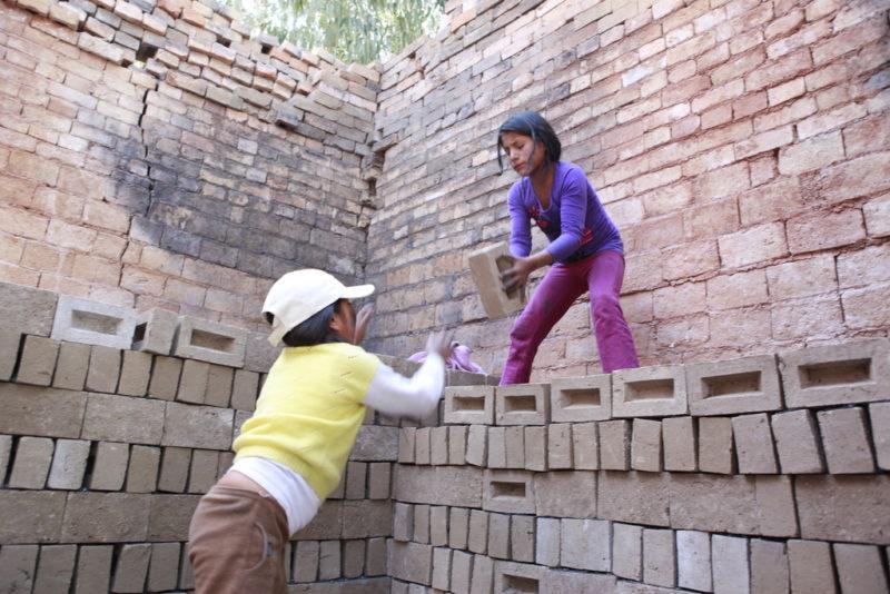 Zwei Mädchen stapeln in Kinderarbeit gefertigte Ziegel im Brennofen einer Ziegelei in Peru - Foto: Christian Herrmanny