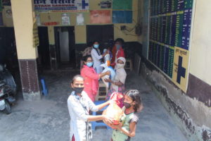 Mit einem Sicherheitsabstand als Schutz vor dem Corona-Virus bekommen die Menschen Grundnahrungsmittel von Helfern überreicht