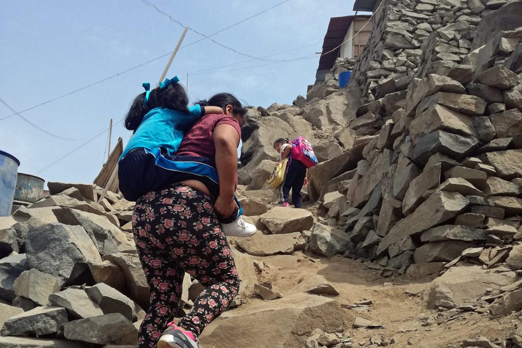 Eine Frau trägt ihre kleine Tochter in einem Armenviertel von Peru, Lima, einen steilen, staubigen Weg hinauf.