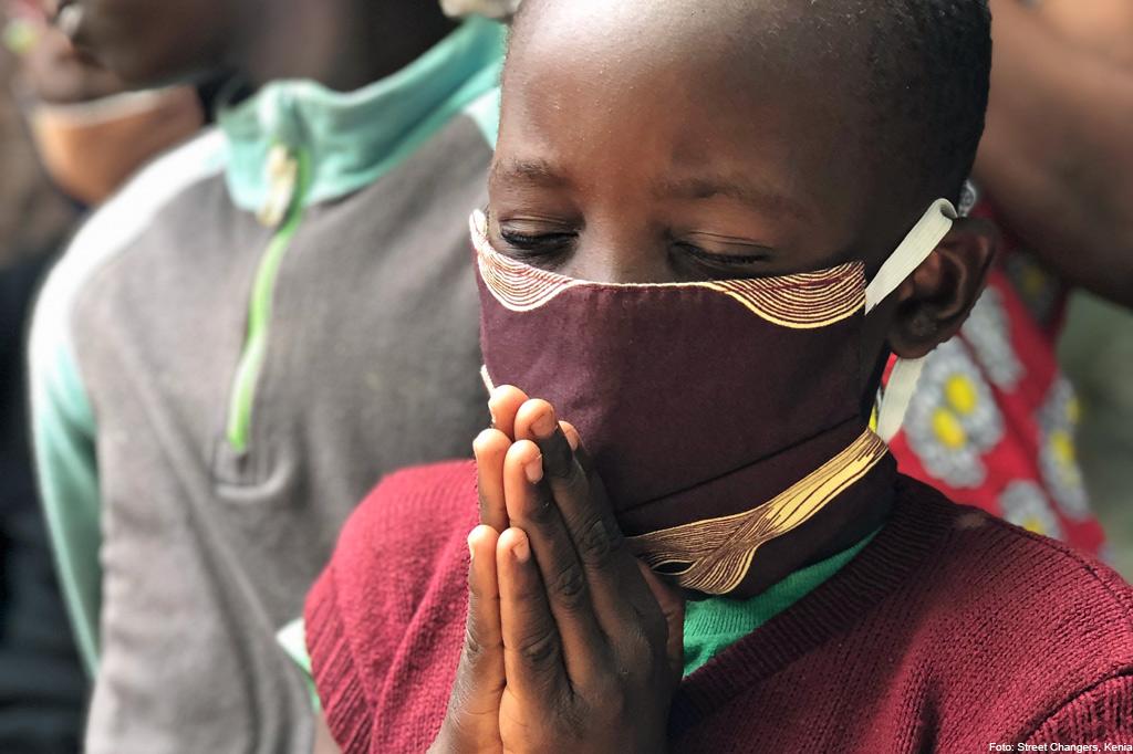 Ein kenianisches Kind mit Maske betet, aus: BMZ-Soforthilfeprogramm - viel Potenzial für Kinderrechte