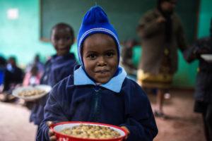 Schulmädchen aus Kenia mit einem vollen Teller: Im BMZ- Soforthilfeprogramm ist die Finanzierung von Schulmahlzeiten ein wichtiger Bestandteil