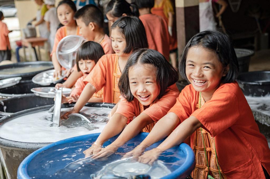 Schulkinder in thailand haben Spaß beim gemeinsamen Abwasch.