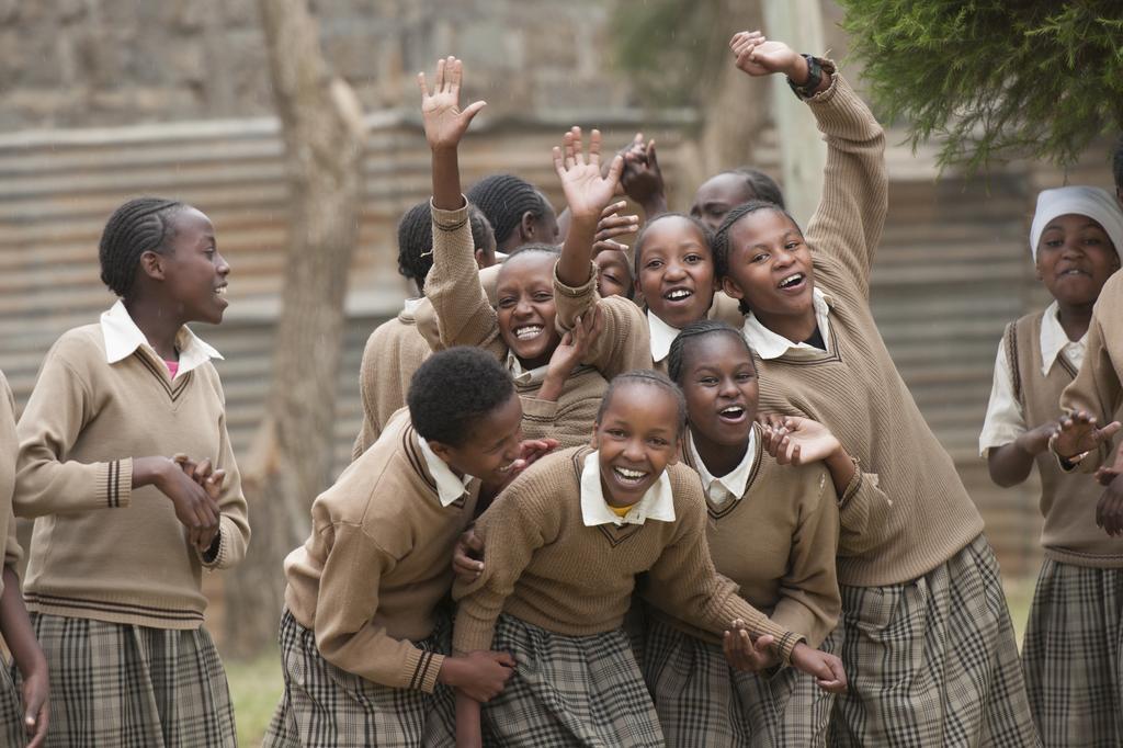 Jubelnde Mädchen in Schuluniform in Kenia. Die Mädchen sind Mitglied eines Schülerparlaments - <auch eine Art Kinderrechtsausschuss