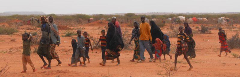 Eine äthiopische Familie zu Fuß unterwegs in der Savanne. Sie flieht vor einer Dürre