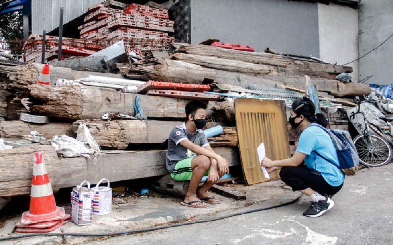 Eine Sozialarbeiterin unseres Partners BDF spricht mit einem Jugendlichen auf einer Baustelle in Thailand über die Auswirkungen der Corona Krise