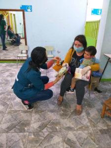 Eine Projektmitarbeiterin bietet einer Mutter Spielzeug für ihren kleinen Sohn an