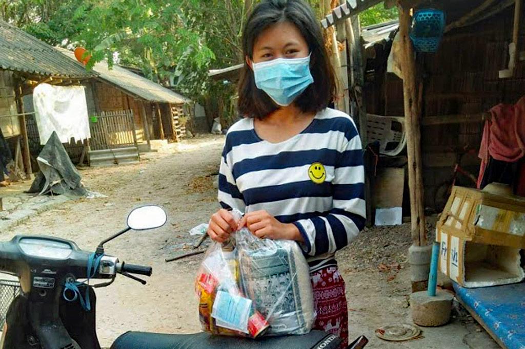 Die 17-jährige Nong Bae mit einer Lebensmittelspende in ihrem Dorf