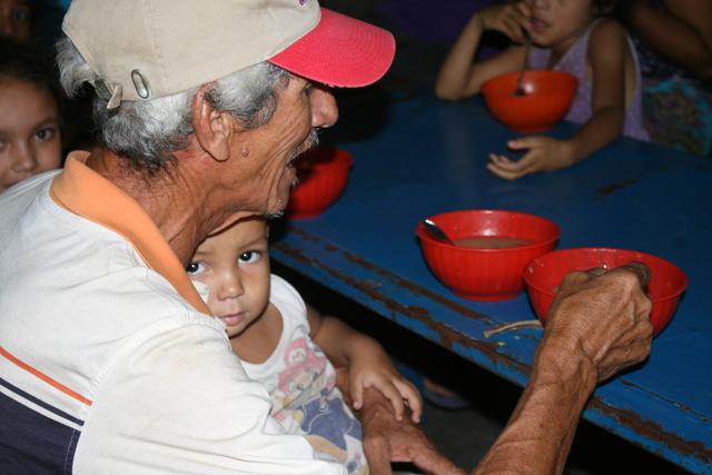 Ein alter Mann füttert ein Kind auf seinem Schoß. (Quelle: Jürgen Schübelin)