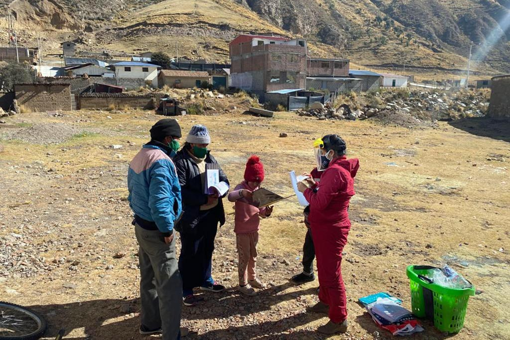 Zwei Kinder und ihre Eltern erhalten wegen der Schulschließungen das Unterrichtsmaterial geliefert. Im Hintergrund ist ein pruanisches Hochlanddorf zu sehen.