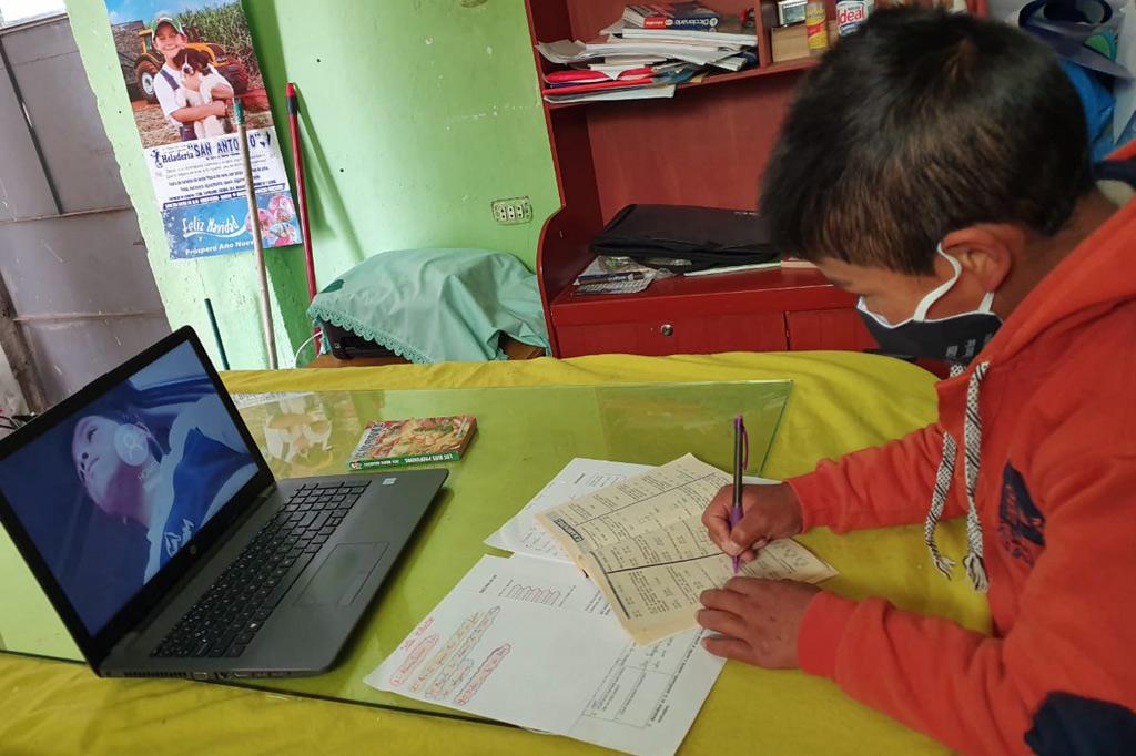 Ein Junge schreibt in ein Heft, Vor ihm auf dem tisch steht ein Laptop.