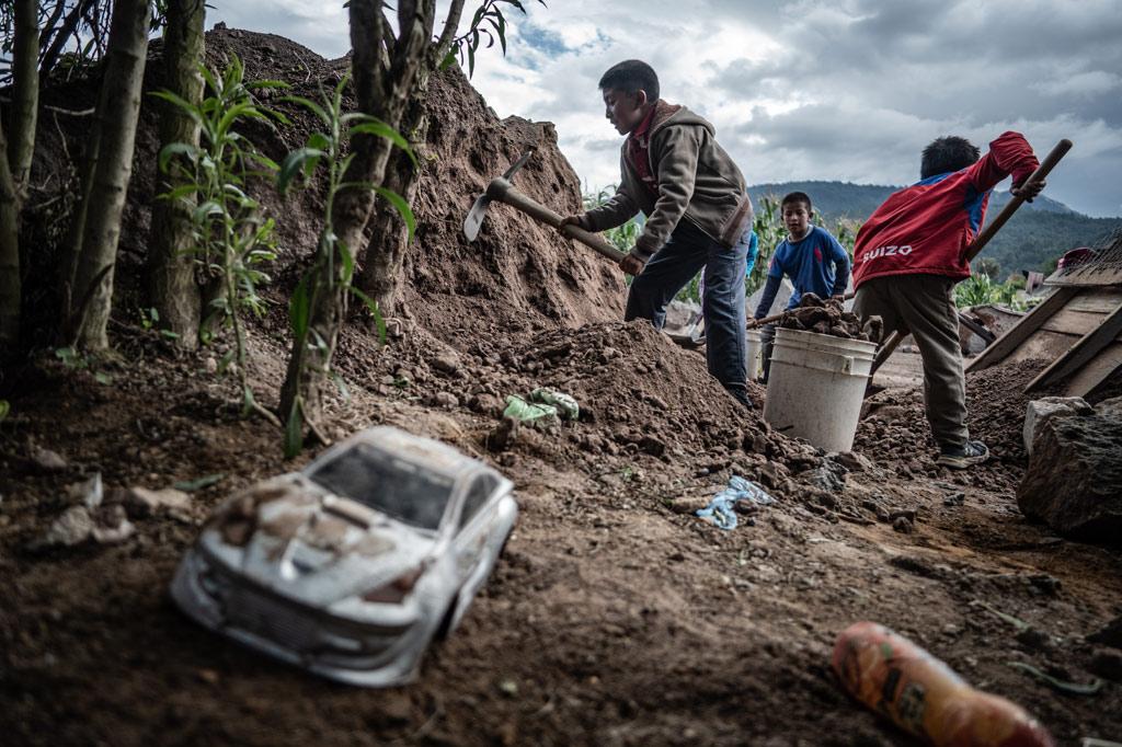 Arbeitende Kinder in einem Steinbruch in Guatemala. Im Vordergurnd ein verdrecktes Spielzeugauto