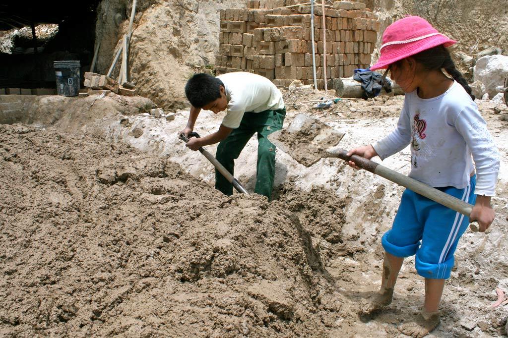 Kinder schaufeln schweren Lehmschlamm in einer Ziegelei in Guatemala