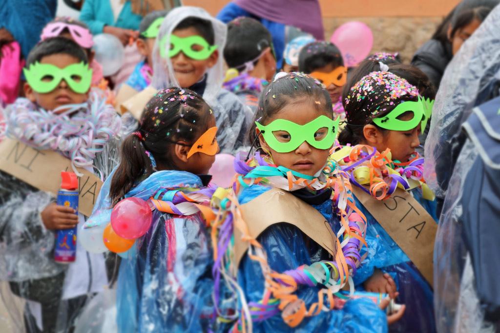 Mädchen in bunten Kostümen mit selbst ausgeschnittenen Brillenmasken