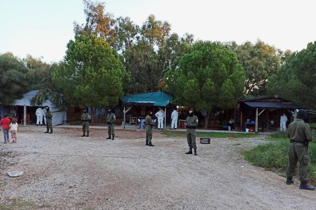 Polizisten in Kampfmontur riegeln das Geflüchtetenlager nach außen ab.