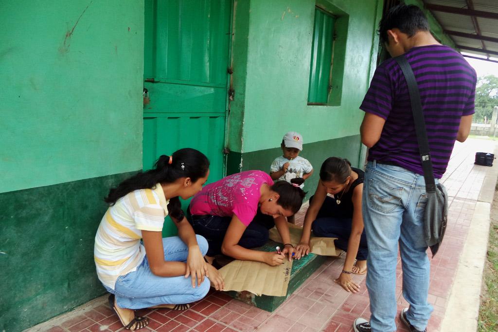 Jugendliche einer Arbeitsgruppe für Kinderrechte hocken am Boden und beschriften ein Plakat