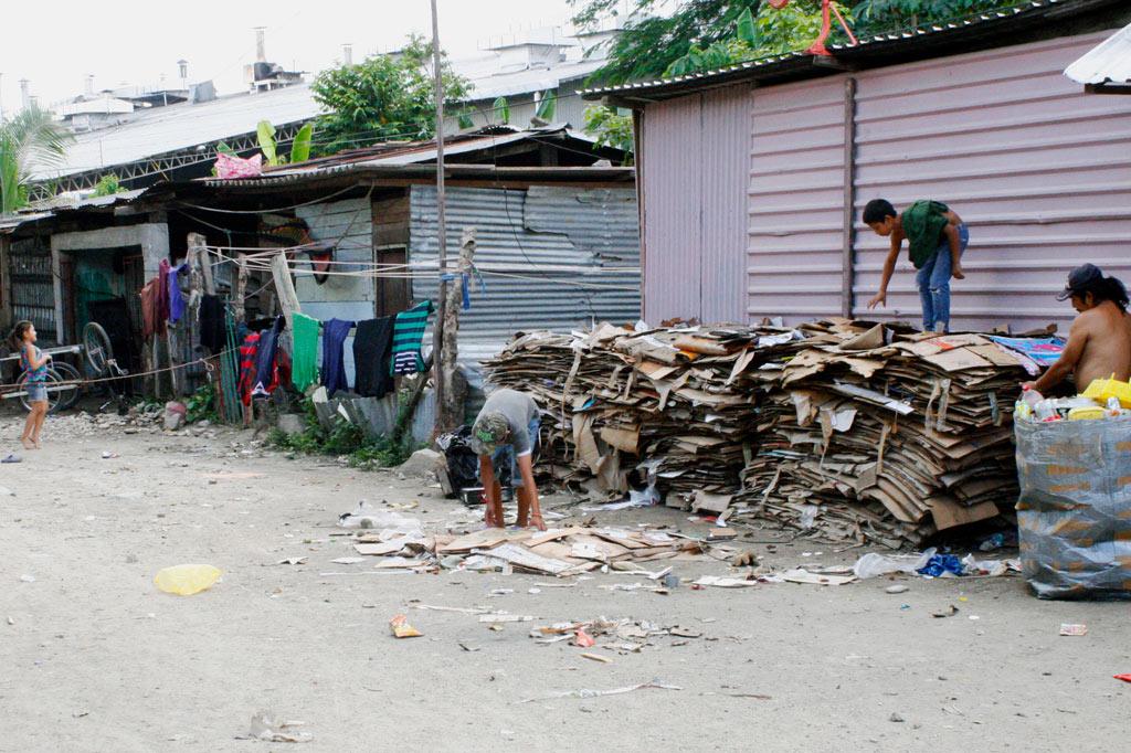 Wellbelchhütten an einer Straße in Honduras. Im Hintergrund sortiert ein Kind Altpapier.