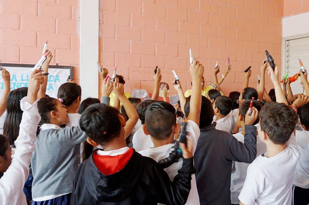 Kinder halten Spielzeugpistolen in die Höhe: Übung zur Gewaltprävention in einer Grundschule in Tegucigalpa. Kinderrechte kommen hier meist zu kurz.