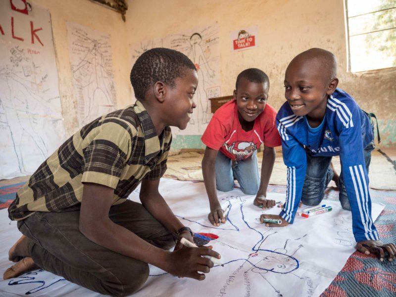 Arbeitende Kinderbeim Body Mapping. Diese zeichnerische Methode veranschaulicht die Probleme und Gefahren von ausbeuterischer Kinderarbeit.
