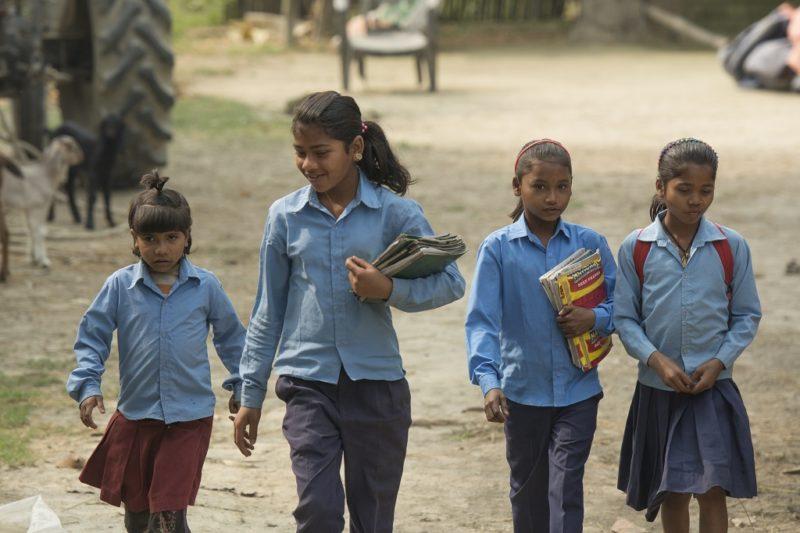 Vier Mädchen in Schuluniformen auf ihrem Schulweg