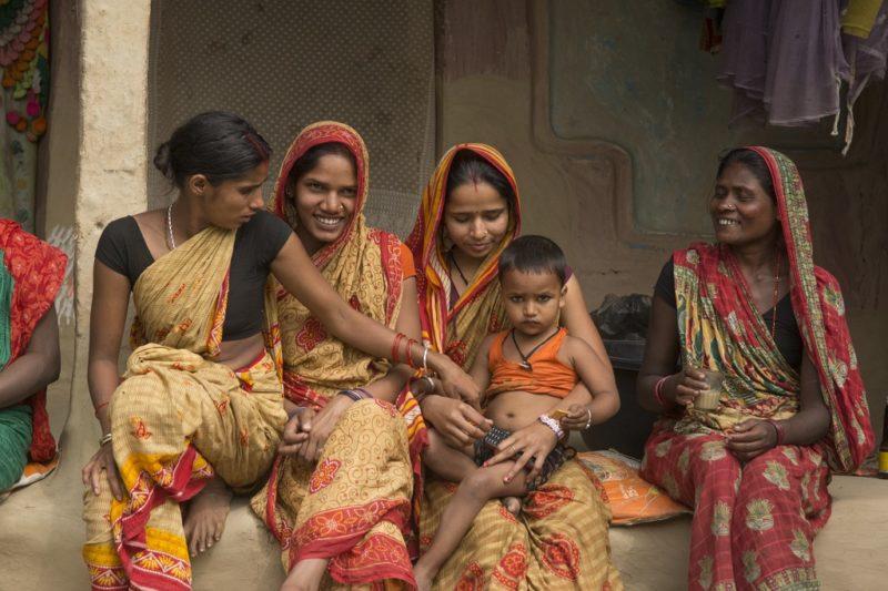Selbsthilfegruppen gegen Frühverheiratung: Vier Frauen sitzen nebeneinander in typisch nepalesischen Gewändern. Eine hält einen kleinen Jungen auf dem Arm. Zwei Frauen lächeln und sehen fröhlich aus.