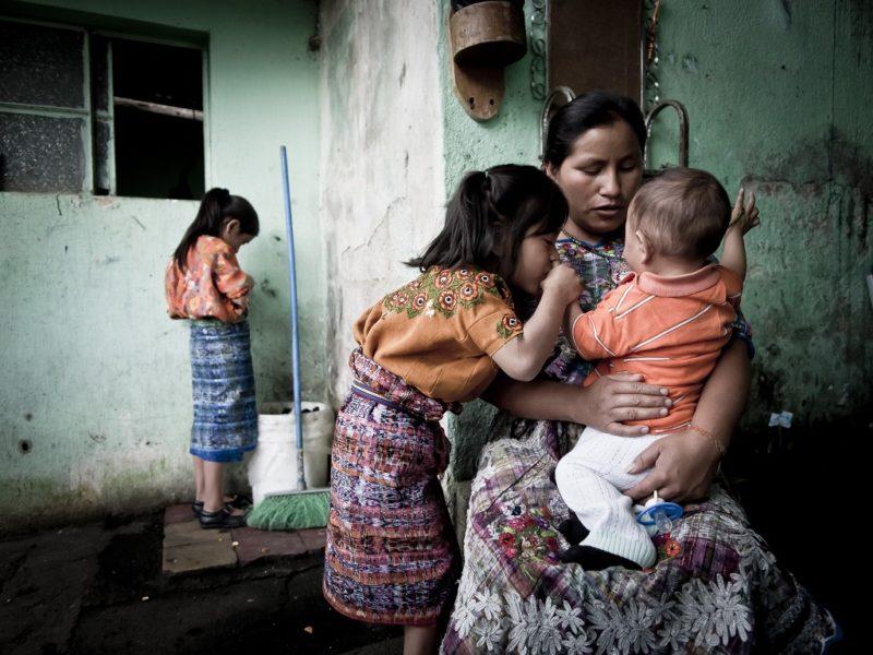 Eine junge Mutter hält in ihrem Haus ein Baby auf dem Arm, ein Mädchen steht dicht bei ihr und dem Kleinkind, ein weiteres hinten in der Zimmerecke
