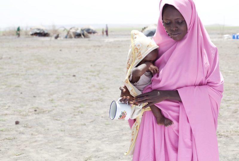 Frühverheiratung betrifft auch diese Frau im rosafarbenem Gewand. Sie steht mit ihrem Baby auf dem Arm in einer kargen Wüstenlandschaft und blickt zu Boden.