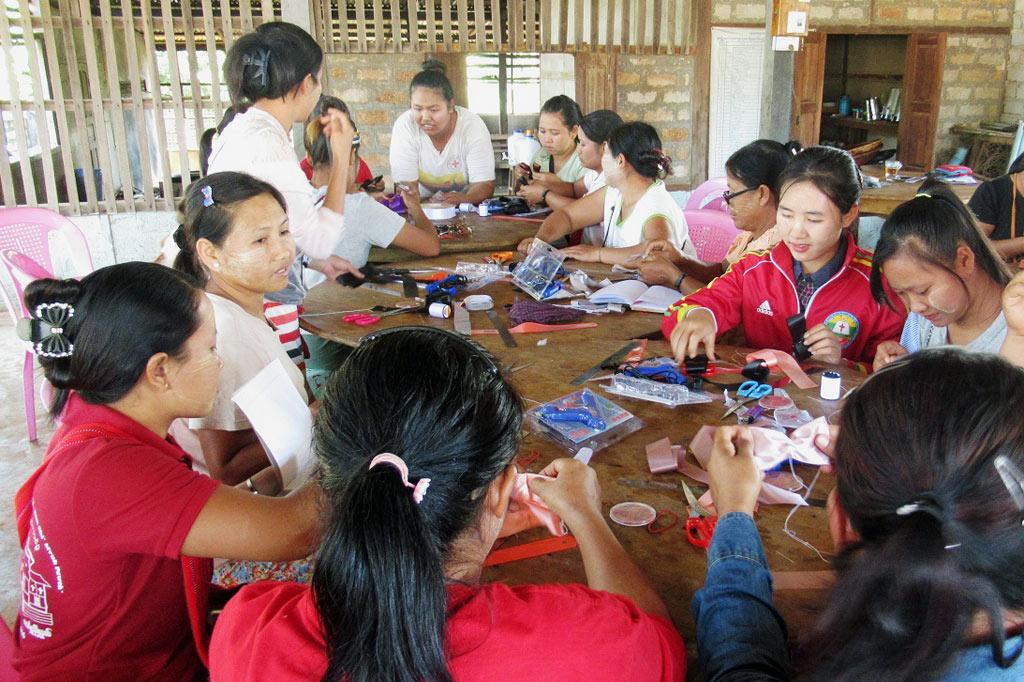 Frauen einer Selbsthilfegruppe sitzen unm einen Tisch und basteln