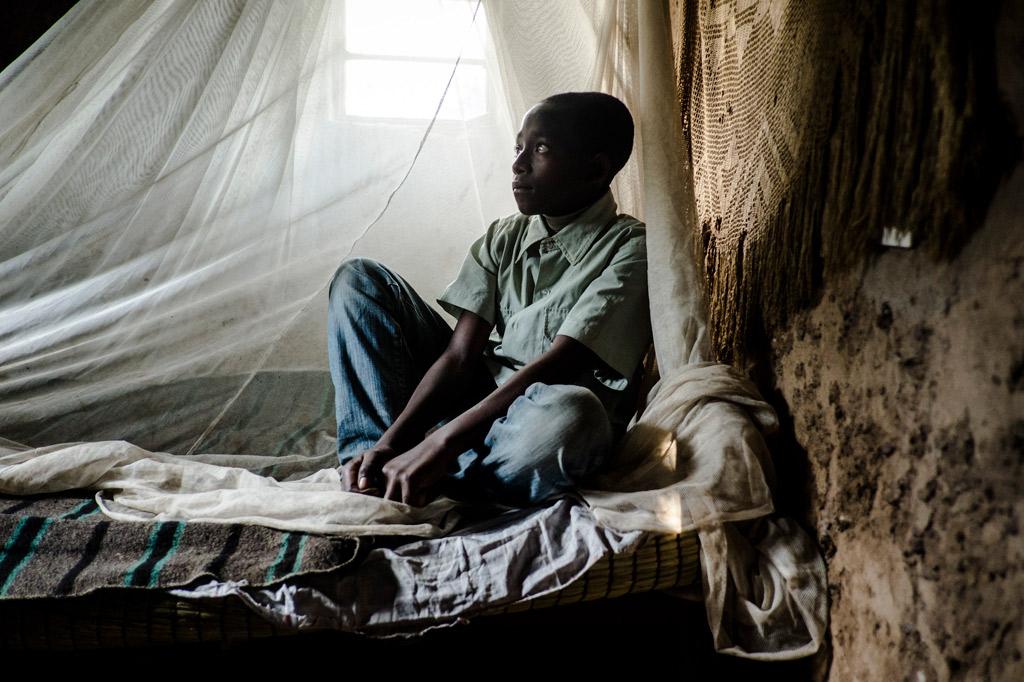 Ein Junge in ruanda sitzt auf seinem Bett. Von der Decke hängt ein Moskitonetz.