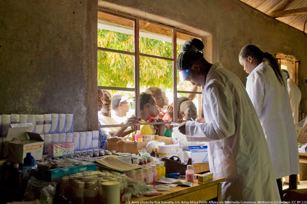 Medikamentenausgabe in Kenia: Gesundheitspersonal versorgt wartende Menschen durch ein Fenster eines Gesundheitszentrum mit Prophylaxe-Mitteln gegen Malaria